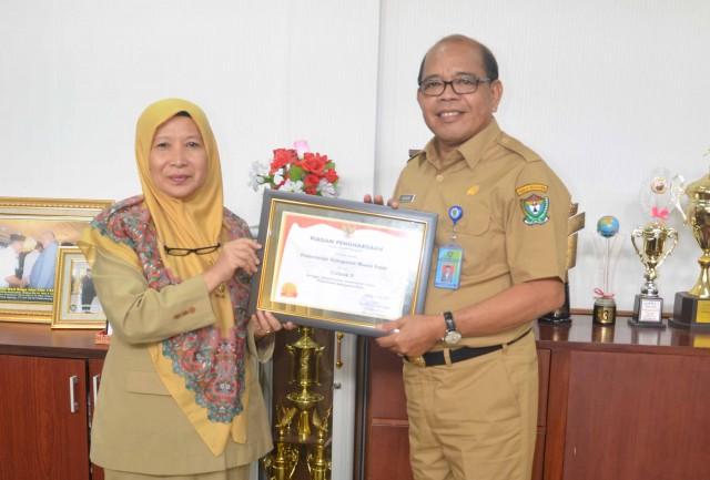 Sekda Muara Enim, Hasanuddin, menerima piagam BKN Award 2016 dari Kepala BKD Muara Enim, Herawati.
