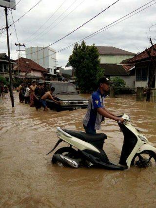 Seorang warga mendorng motor miliknya yang terendam air.