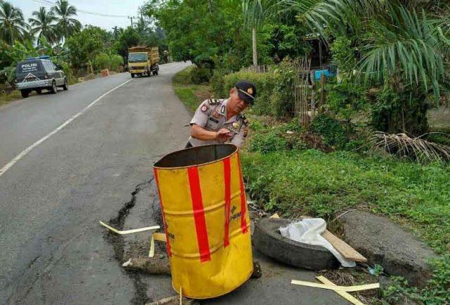Polisi memasang drum di jalan amles Desa Gunung Terang, Kecamatan Gunung Megang, Kabupaten Muara Enim,